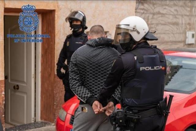 Imagen de uno de los detenidos, custodiados por la Policía Nacional
